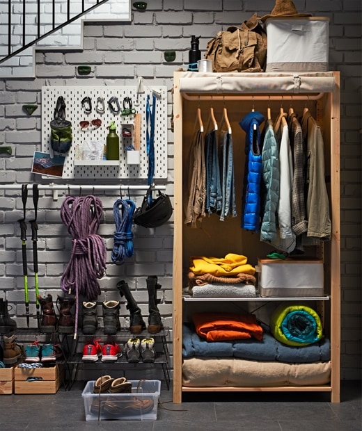 An IKEA IVAR shelving unit in solid pine with a rolled-up cover, and clothes on hangers and blankets inside.