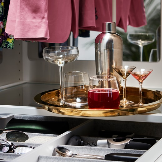 Drinks are standing on a round IKEA GLATTIS tray in brass-colour with a high edge around it.