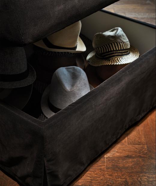 A dark grey FÄRLÖV footstool with storage with hats inside.