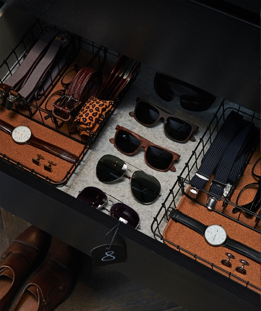 Two PLEJA desk organisers in black steel and cork used for organising belts, watches, glasses and suspenders in a drawer.
