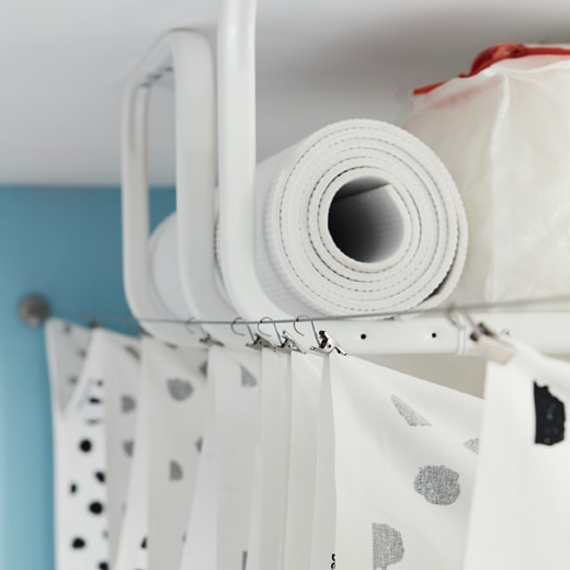 幾個裝在天花板的白色MULIG掛衣架,再用作貯物,並藏在掛在兩條窗簾繩之間的布簾背後。