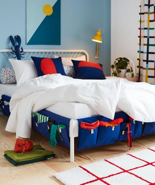 掛在床邊的藍色MÖJLIGHET布製床邊貯物袋可收納襪子和吊帶等物品。