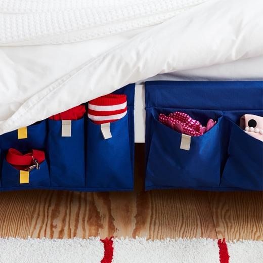 藍色MÖJLIGHET布製床邊貯物袋掛在床邊,方便收納雜物。