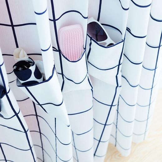 白色和藍色宜家家居ROSALILL窗簾附有口袋,方便收納眼鏡、化妝掃和其他小物。