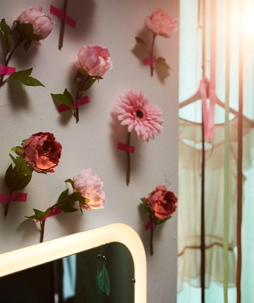 以粉紅色膠紙逐一貼上SMYCKA人造花的牆壁。