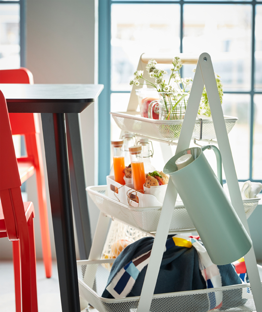 A white RISATORP steel trolley with a wooden handle, filled with a complete breakfast for two.