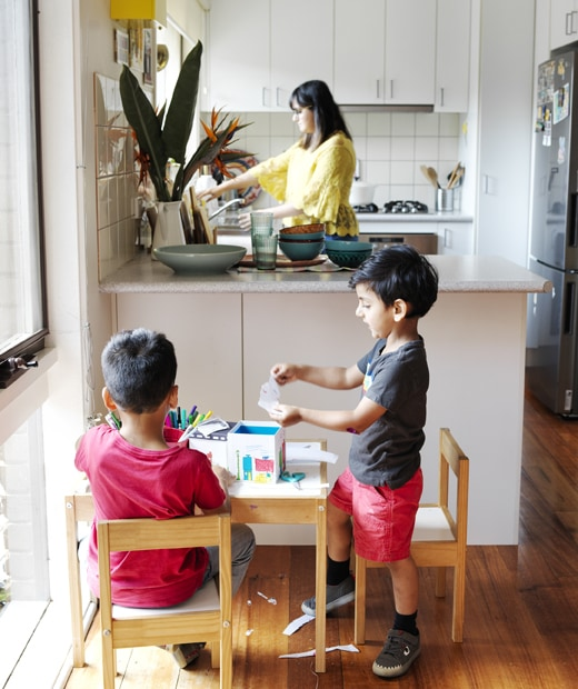 Two children doing crafts at a small table in front of an L-shaped kitchen, where Abeer stands at the sink.