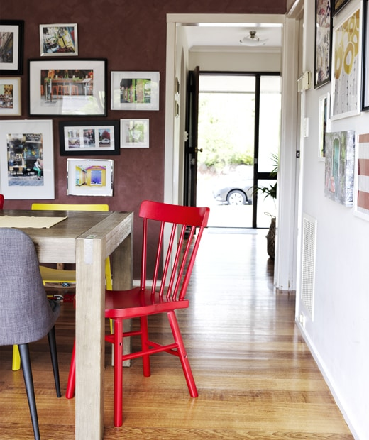 Colourful chairs around a wooden table and a dark red wall with picture gallery and a doorway into the hall.
