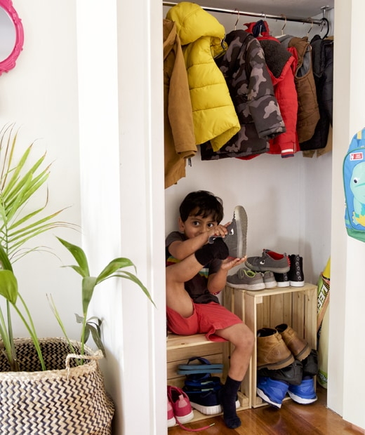 A small child putting shoes on and sitting on a wooden crate below coats hanging in a cupboard.