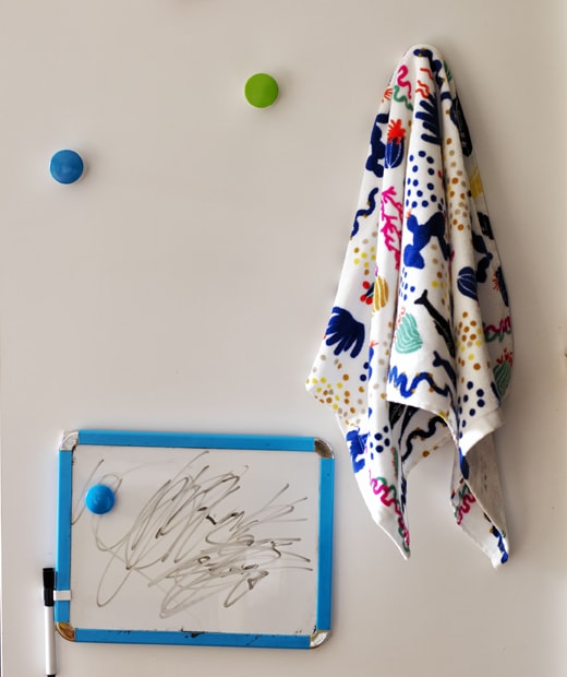 A small whiteboard with pen and patterned material hanging on colourful hooks.