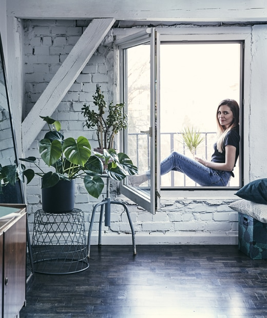 Katarzyna sitting outside the window of a room with white painted brick walls and plants.