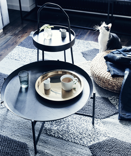 Two dark side tables and a rattan footstool on a grey textured rug.