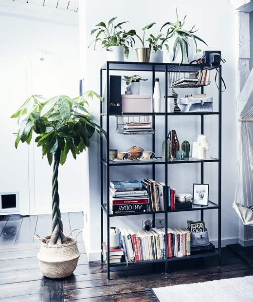 Books, plants, and ornaments on a black open storage unit next to a large plant in a rattan basket.