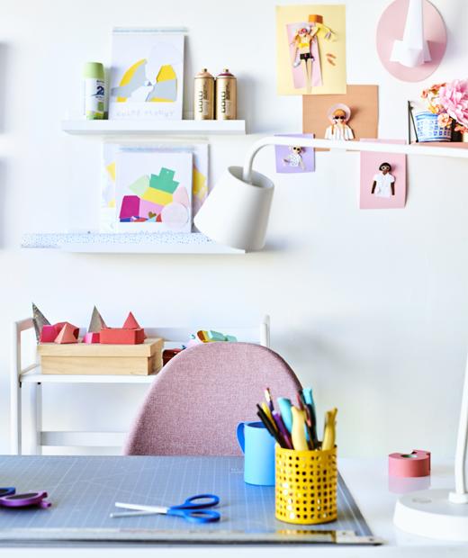 放在書檯上的筆筒和白色檯燈,配以粉紅色椅子,背後的牆上有一個層架,擺放了藝術品。