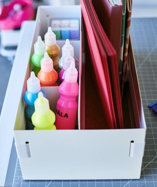 放在白色座檯貯物架內的顏料及記事簿。