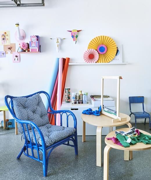 兩張木角几上的織布機和布料,旁邊有一張藍色扶手椅,白牆上則有色彩奪目的藝術品。