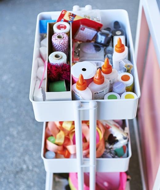 白色三層活動几放滿各種手工用品,包括絲帶、繩及膠水。