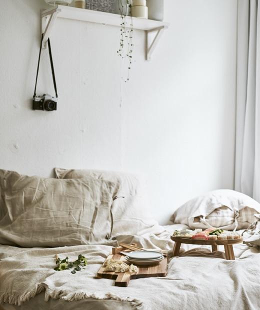 睡床鋪上中性色調的寢具,上面擺放木砧板盛載壽司,上方的白色牆上有一個層架。