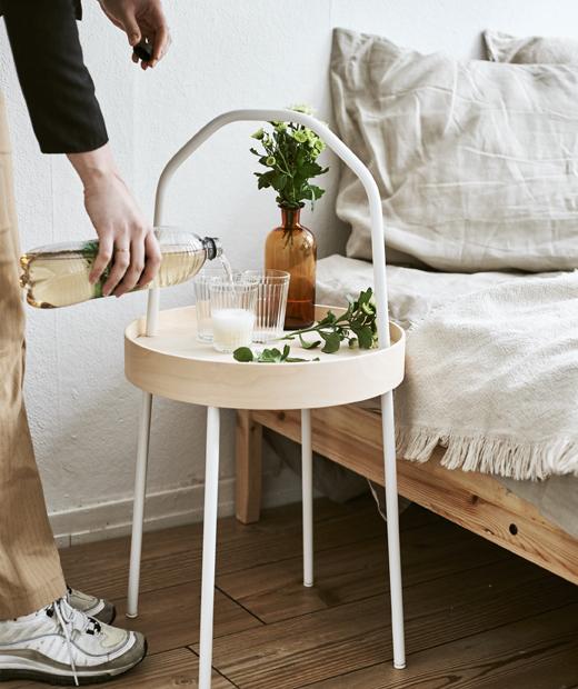 床邊有一張附有白色手柄的淺木色茶几,Yvet將飲品倒進茶几上的水杯。