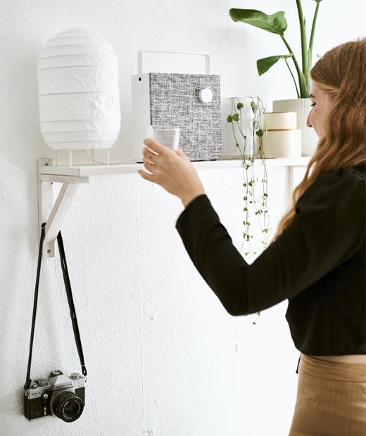 Yvet將杯放在層架上,架上有燈、揚聲器及植物。