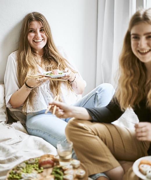 Yvet與朋友圍坐在床上分享壽司。