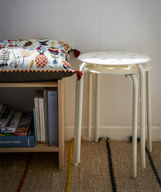 Two white stools stacked up next to a low bookshelf with a seat cushion on top.