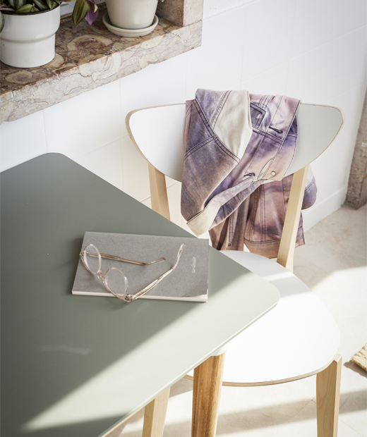 A close-up of a grey table and white chair bathed in sunlight.