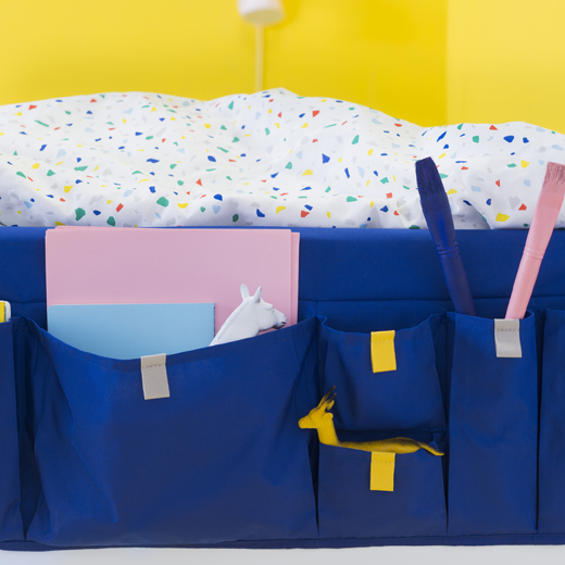 Some colourful bedding and a blue bed pocket filled with notebooks against a yellow background.