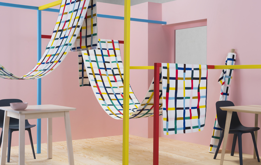 Multicolour patterned fabric draped across colourful frames in a pink room.
