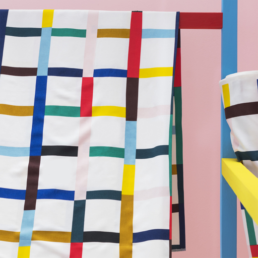 A close-up of multicolour patterned fabric draped across a rail.