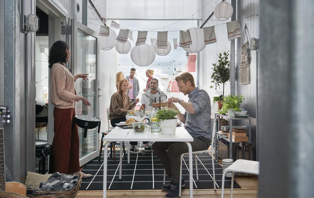在兩個貨櫃之間的空間,幾個人聚在放滿食物的長檯旁邊,上方掛著紙燈籠。
