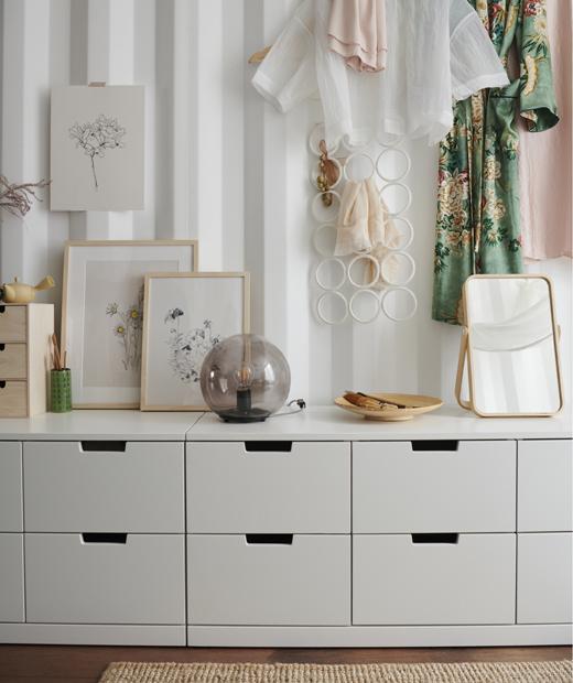 擺放照片的矮身白色貯物組合,上面有一盞檯燈及一面鏡子,上方掛著衣物,背後是白色波紋牆。