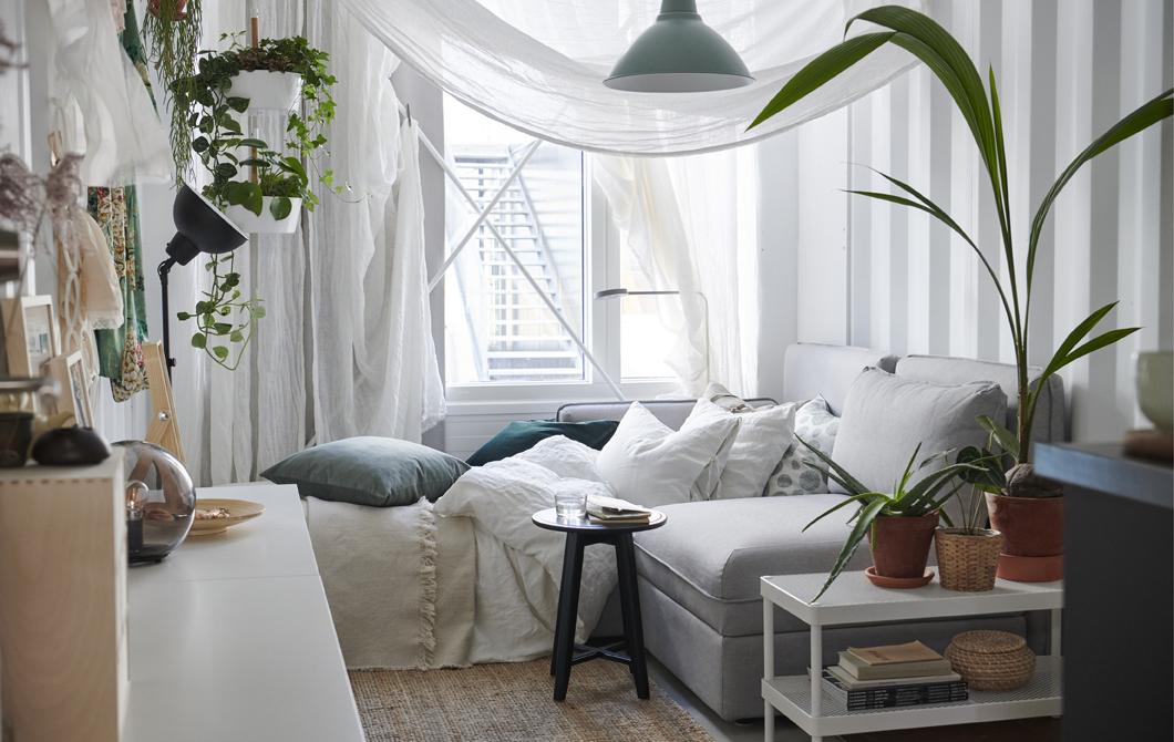 採用中性色調布藝產品的白色睡房,窗紗披在梳化床旁邊,房內放有盆栽。