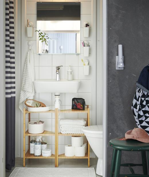 浴室洗手盆下設有木層架,牙刷則放在白色掛牆容器內。