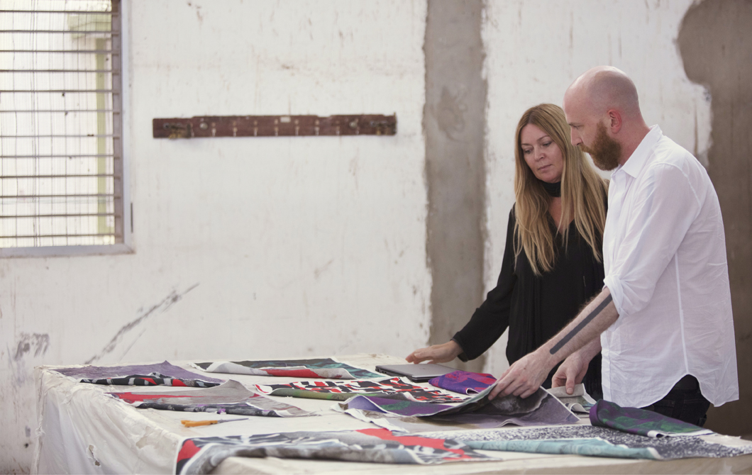 Karin Gustavsson and Martin Bergström looking at colourful fabrics on a large table.
