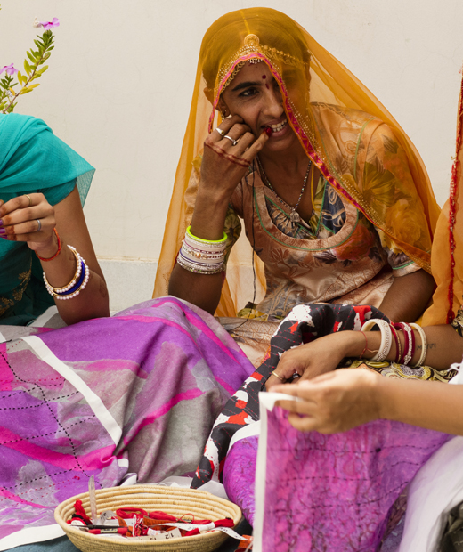 Three people sitting and working on colourful fabrics together.