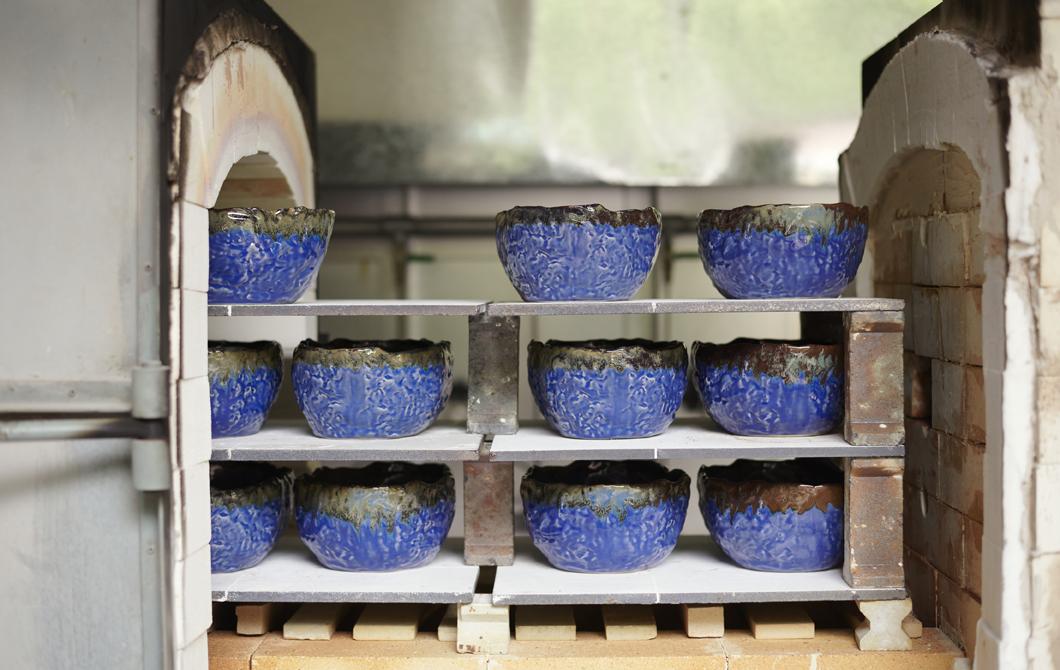 Rustic blue bowls on shelves of a brick kiln.
