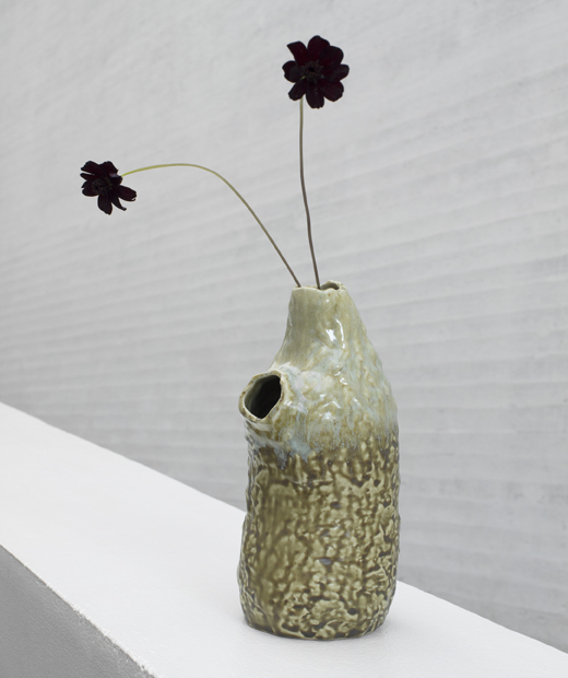 A rustic vase with black flowers in one of two small openings.
