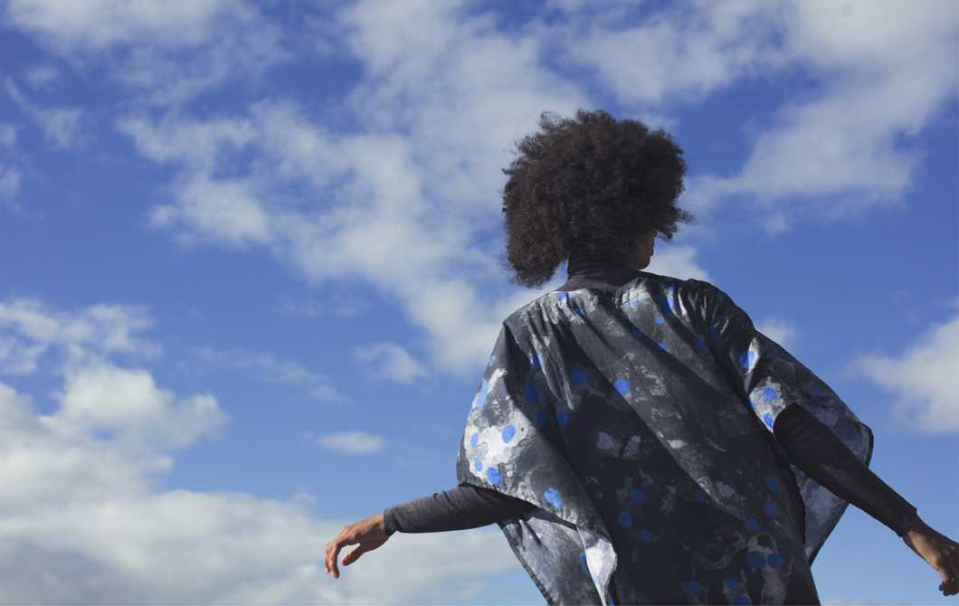 A person wearing a patterned black, blue and white kaftan standing against a blue sky.