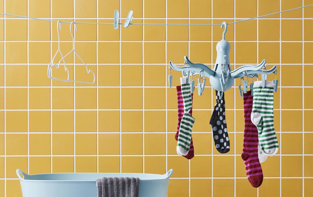 掛在藍色曬衣架上的襪子,曬衣繩上還有一些衣夾及衣架,背後是黃色瓷磚牆。