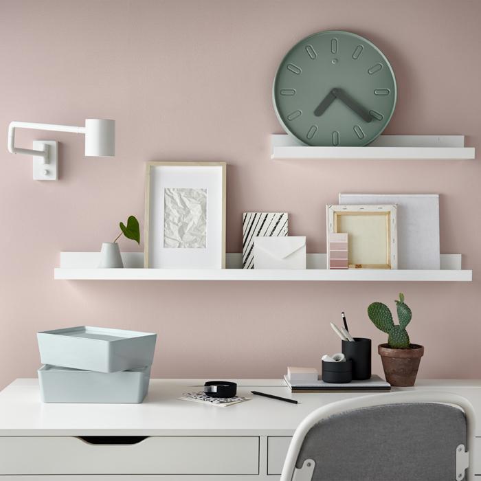 粉紅色牆前的白色書檯,白色層架上放有照片及時鐘。