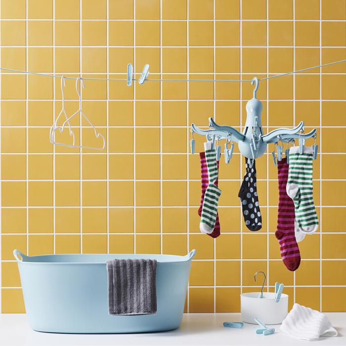 掛在藍色曬衣架上的襪子,曬衣繩上還有一些衣夾及衣架,下面有一個藍色洗衣籃,背後是黃色瓷磚牆。