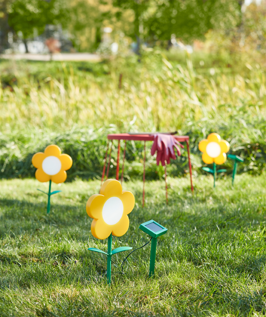 Three yellow SOLVINDEN LED solar-powered outdoor flower lamps on a lawn in summer.