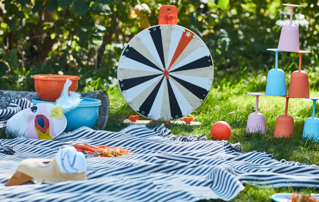 放在野餐墊上的LUSTIGT木製幸運輪盤遊戲、其他玩具和不易碎餐具。