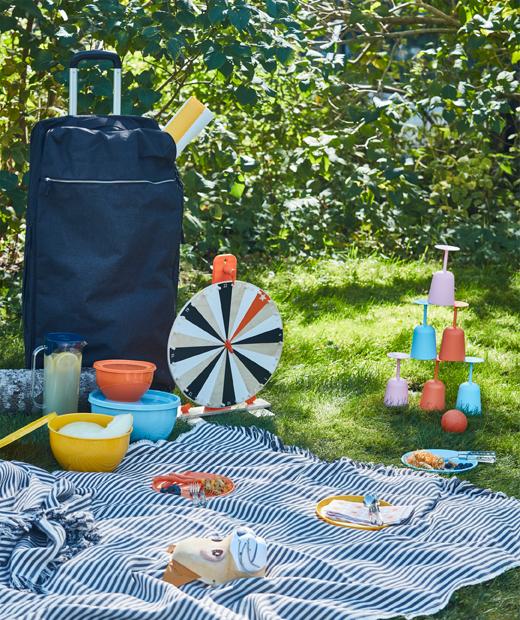 草地野餐,以及以藍色FÖRENKLA XL活動式旅行袋帶來的餐具、玩具及大野餐墊。