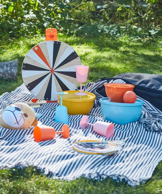 草地野餐及多色塑膠餐具和酒杯。