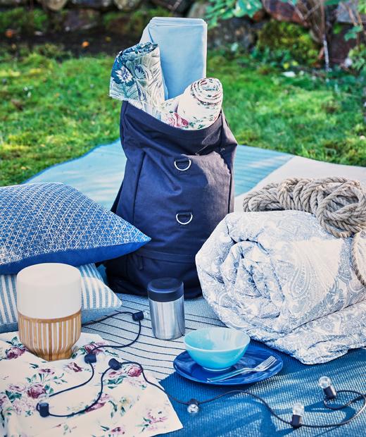 以咕、被及使用電池的LED燈(如MULLBACKA座檯燈)布置的夏日野餐。