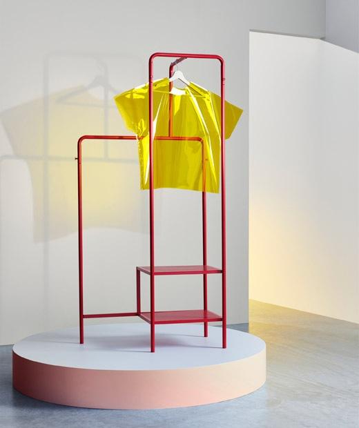 放在台上的紅色金屬衣帽架,上面掛有一件黃色塑膠T恤。