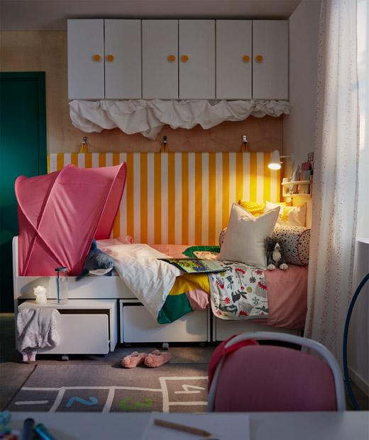 兒童房的睡床一角,床褥掛在後面的牆上,床下方和上方也設有貯物空間。