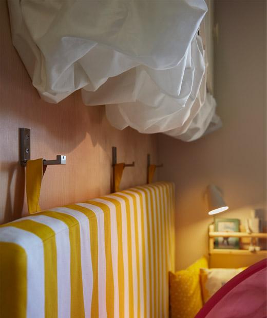 床褥以掛鈎掛在床邊的牆上,貯物櫃下方掛上白色布料,形成雲朵形狀。